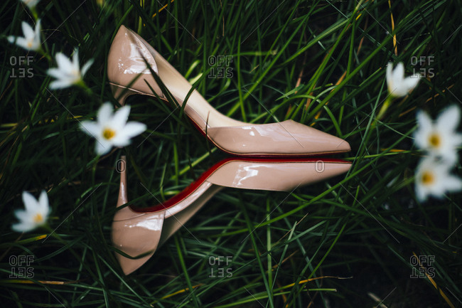 A pair of red-soled wedding heels sit amid blades of grass and flowers
