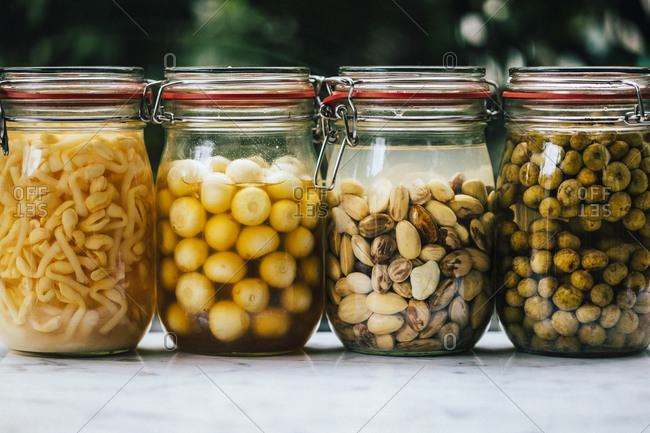 Bean sprouts, garlic, stinky beans, and small figs pickled in glass jars