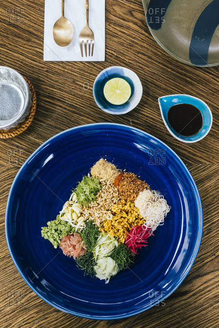 Southern herbs with toasted rice and fish innards dressing on a blue plate at a restaurant in Bangkok, Thailand