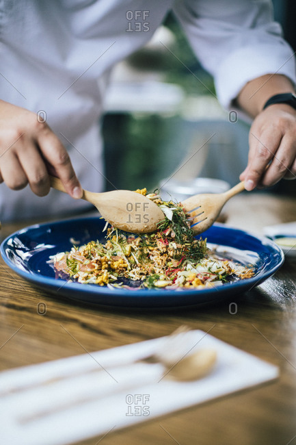 Chef preparing dish of southern herbs with toasted rice and fish innards dressing in a restaurant in Bangkok, Thailand