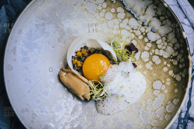 Detail view of egg yolk with mussel sauce and faux shells at an upscale restaurant in Bangkok, Thailand