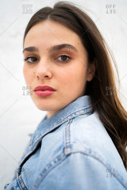 Close up portrait of a beautiful young brunette woman wearing a light blue jean jacket and looking at camera