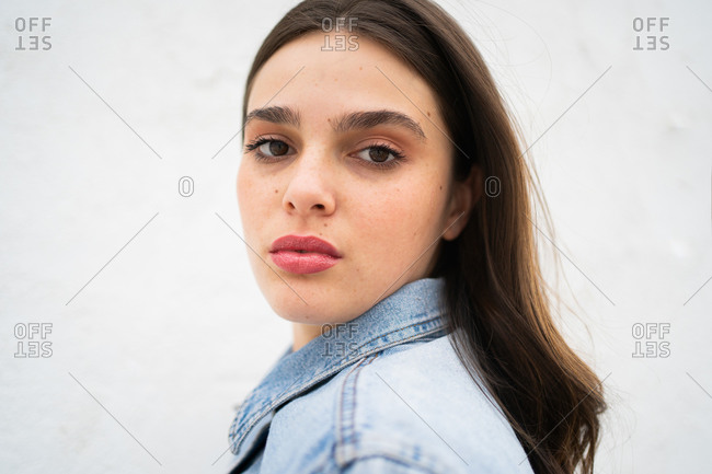Young brunette woman wearing a light blue jean jacket and looking at camera close up