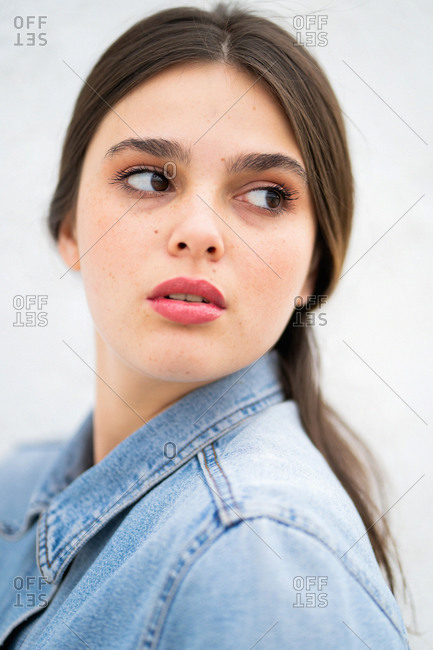 Close up of a young woman wearing a light blue denim jacket looking away in front of light background