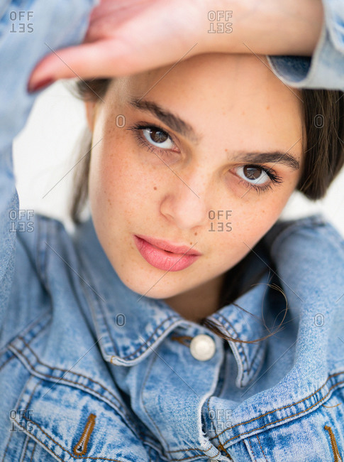 Portrait of a beautiful young woman wearing a light blue jean jacket with a sultry expression