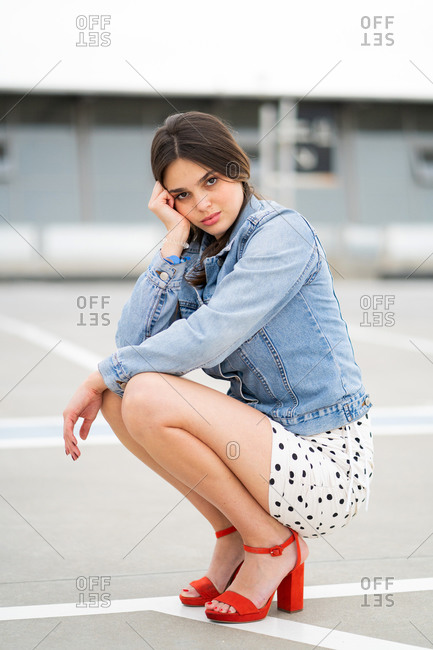 Young woman wearing a light blue jean jacket and polka dot skirt with red heels looking at camera seductively