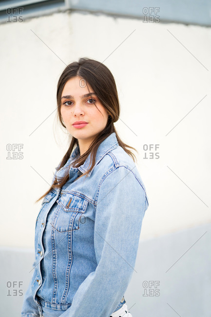 A young brunette woman wearing a light blue jean jacket and looking at camera close up