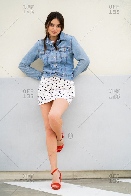 Stylish young woman wearing a light blue jean jacket and polka dot skirt with red heels leaning on building with sultry expression