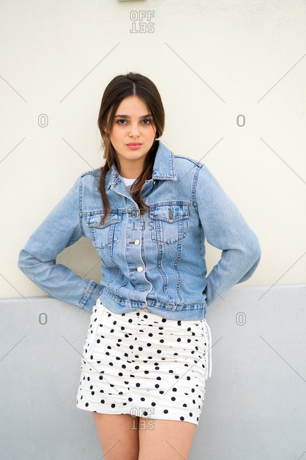 Young woman wearing a light blue jean jacket and polka dot skirt with red heels leaning on building with sultry look on her face