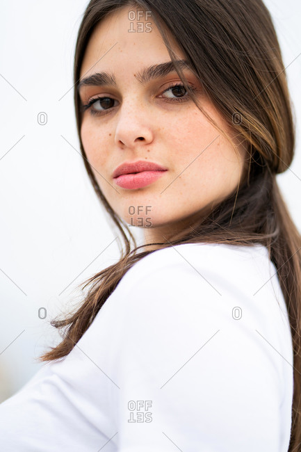 Portrait of a pretty young brunette woman looking over her shoulder at the camera