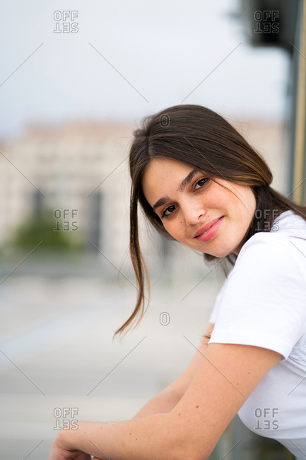 Pretty young brunette woman smiling and looking over her shoulder at the camera