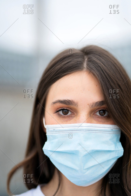 Close up of a pretty young brunette woman wearing a disposable facemask looking at camera