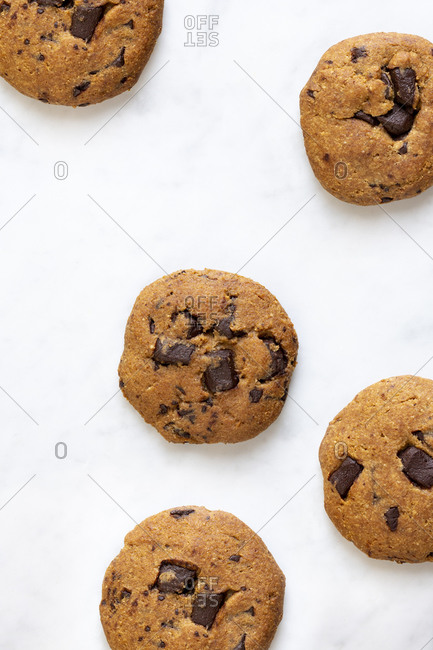 Five chocolate chunk cookies on marble surface viewed from above