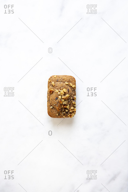 One mini banana bread loaf on white marble surface viewed from above