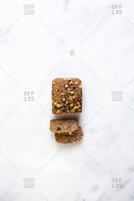 A mini banana bread loaf sliced on white marble surface