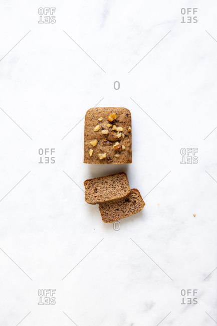 Overhead view of a mini banana bread loaf sliced on white marble surface