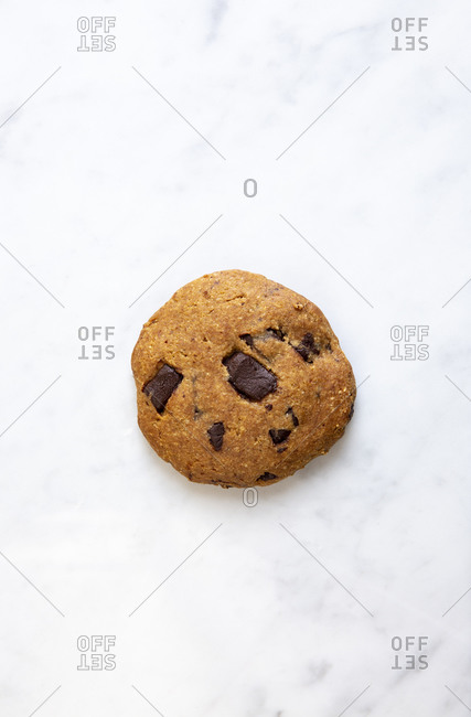 Overhead angle of one chocolate chunk cookie on marble surface