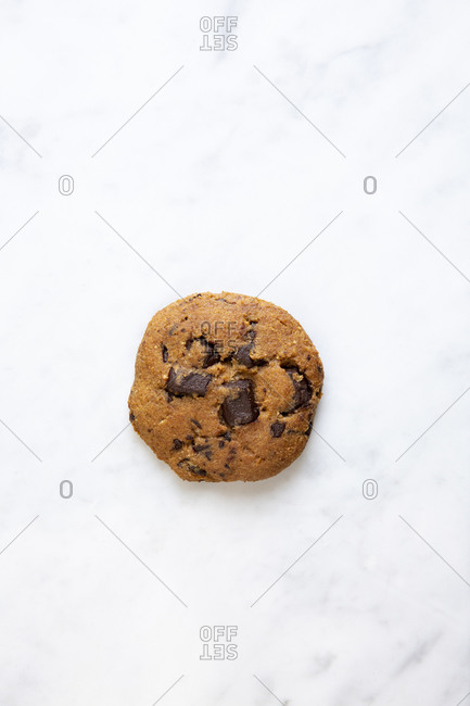 A single chocolate chunk cookie on marble surface