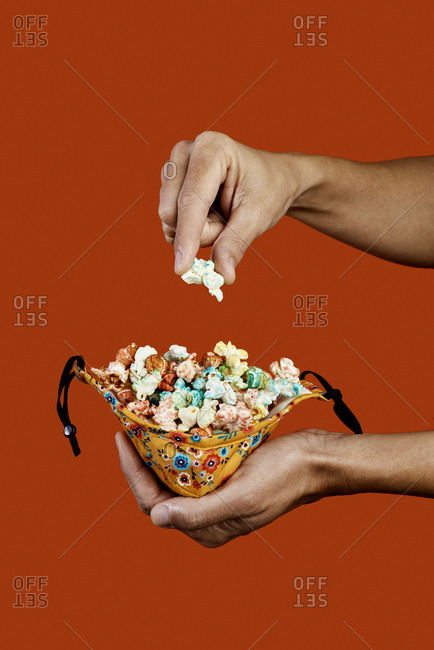 A man takes a candied popcorn from a face mask used as a container, on an orange background