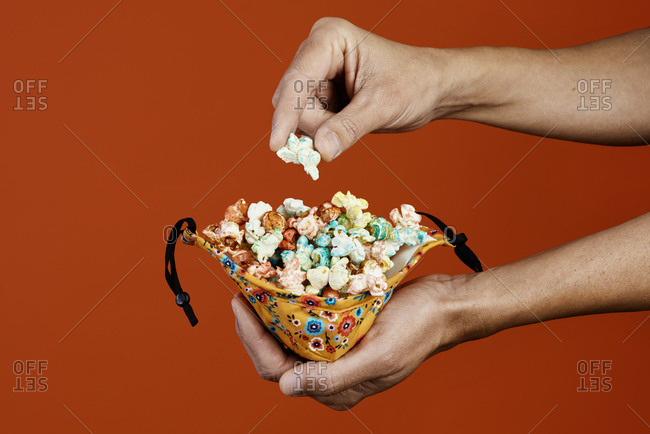 Closeup of a man taking a candied popcorn from a face mask used as a container, on an orange background