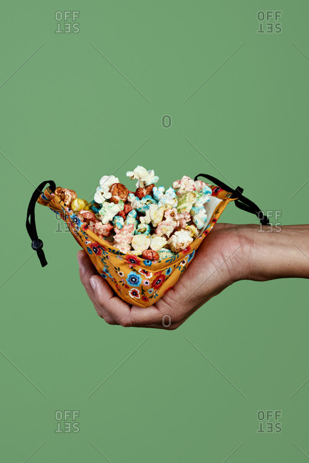 Closeup of a man using a face mask as a container for candied popcorn, on a green background