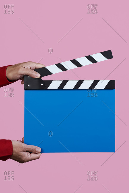 Closeup of a man in red about to clap a blue clapperboard on a pink background