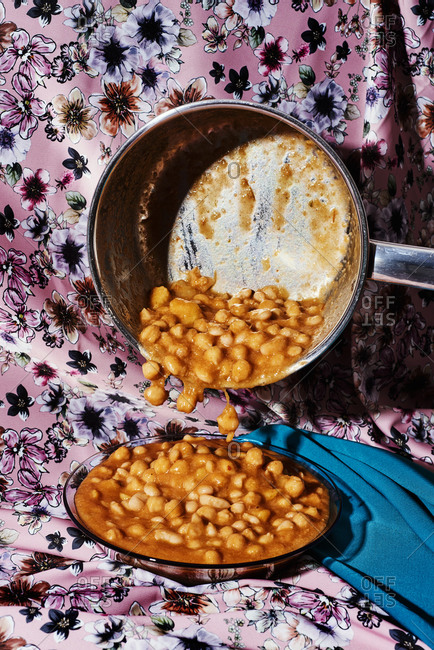 Serving potaje, a Spanish traditional legume stew made with beans and chickpeas, on an orange glass plate placed on a floral-patterned fabric
