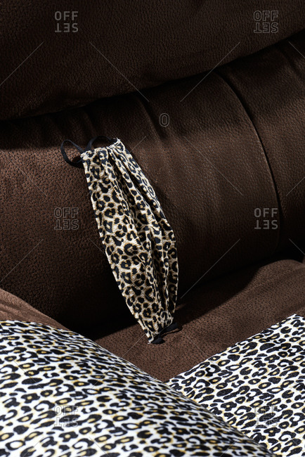 A face mask made with a leopard animal print-patterned fabric, on a sofa