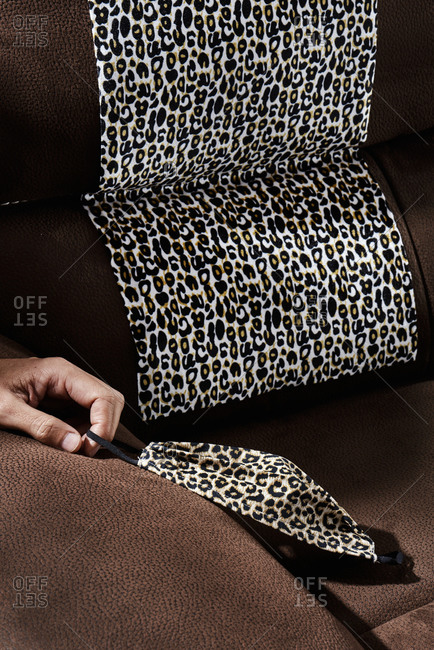 Closeup of the hand of a man holding a face mask made with a leopard-patterned fabric, on a sofa