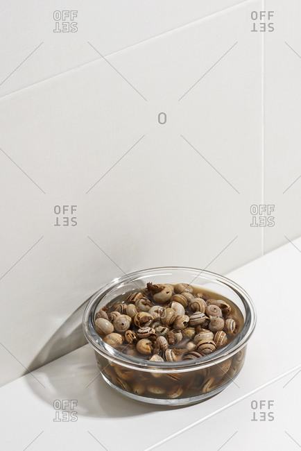 A glass container with Spanish caracolillos en caldo, a recipe of land snails, on a white table, against a tiled wall with some blank space on top
