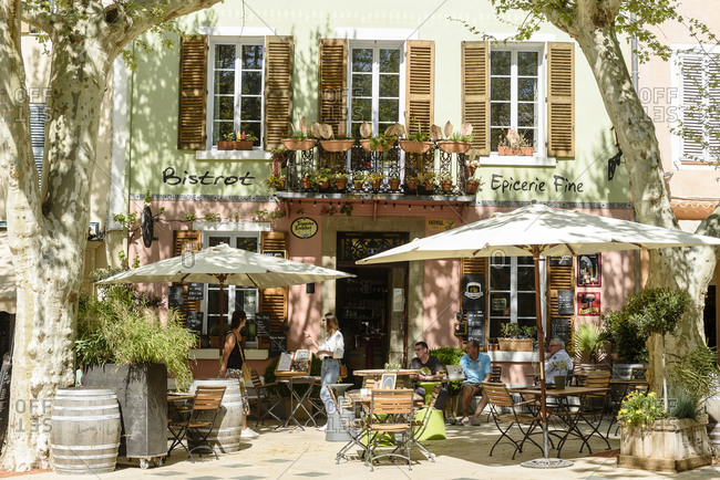 Collobrieres, France - April 20, 2018: Exterior of a pastel colored bistro with outdoor dining