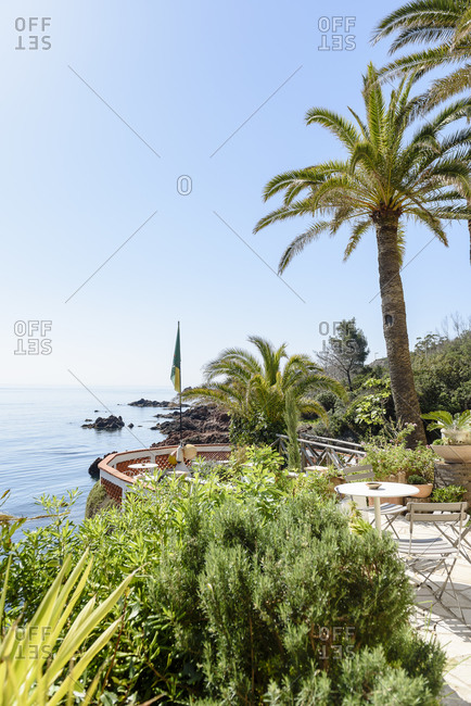 Saint-Raphael, France - April 20, 2018: Restaurant terrace with palm trees overlooking Mediterranean Sea