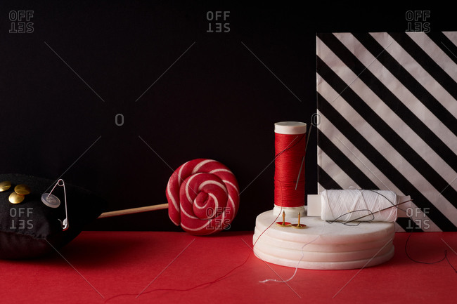 Still life with threads and needles on red and black background