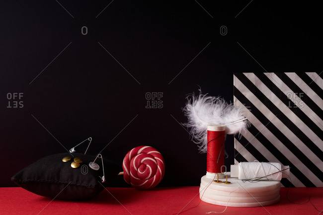Feathers, threads and needles on red and black background