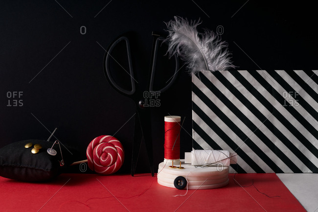 Scissors, feathers, threads and needles on red and black background
