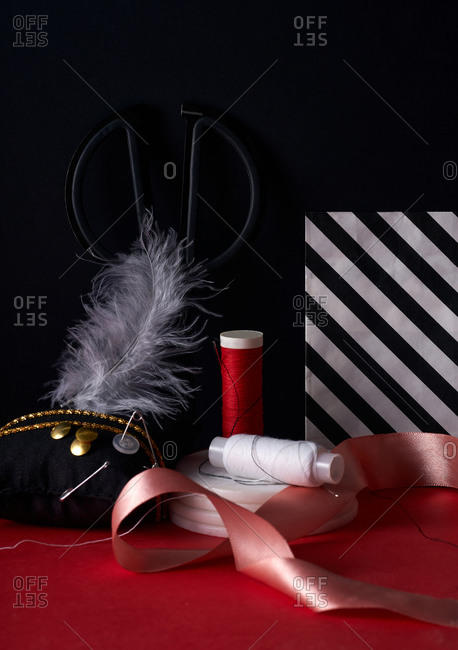 Variety of sewing items and tools on a red and black background