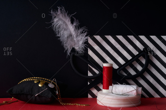 Various craft and sewing items on a red and black background