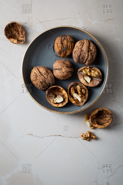 Overhead view of raw walnut in shell in a rustic bowl