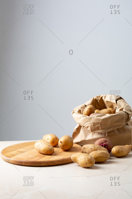 Potatoes in a paper shopping bag and cutting board with copy space