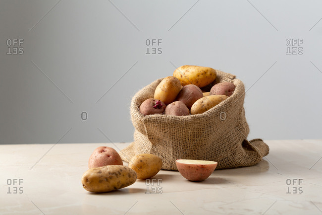 Burlap sack bag full of potatoes on light surface with copy space