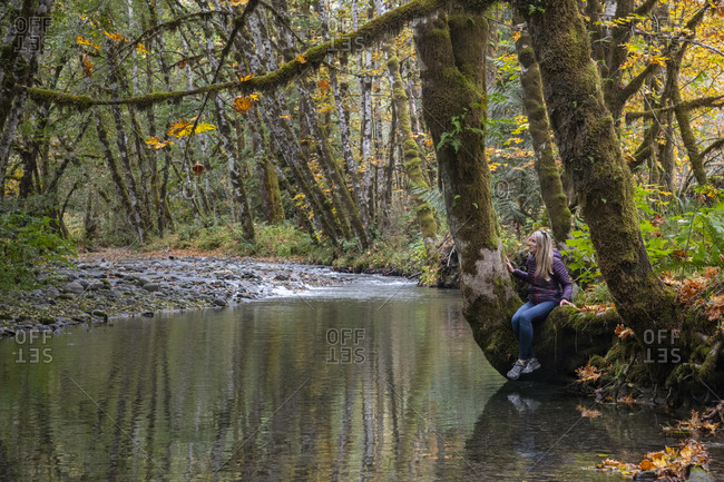 Woman admiring fall colors along a river bank on Vancouver Island, British Columbia