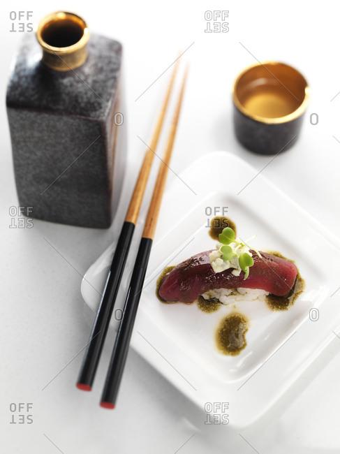 Sake and beautiful plate of bluefin tuna sushi with blue cheese and nori vinaigrette.