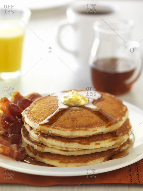 A pancake, bacon breakfast with orange juice and coffee.