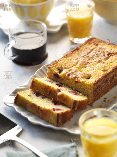 A brunch with raspberry cornbread, orange juice and coffee.