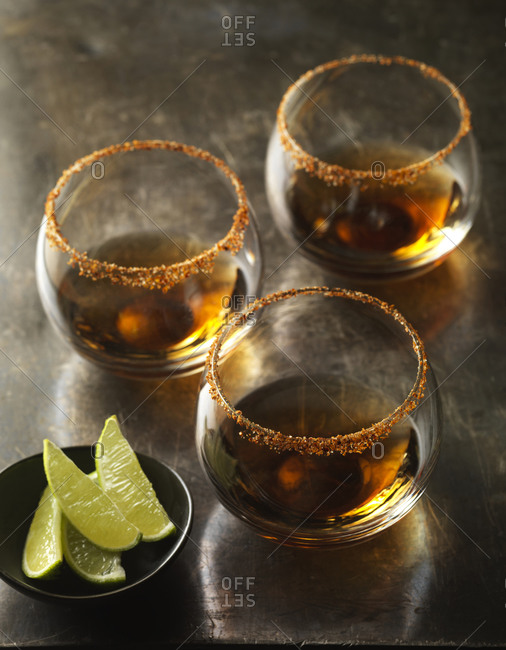 Three glasses of premium tequila with spicy salted rims & lime wedges.