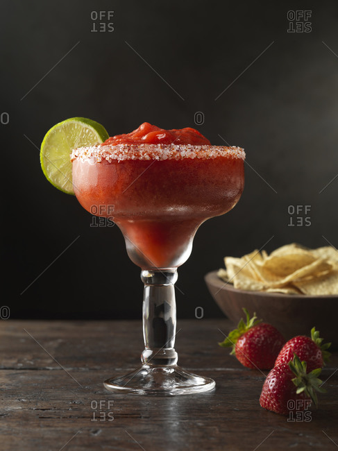 Frozen strawberry margarita with lime & tortilla chips.