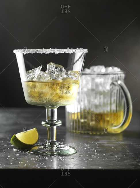 A glass of tequila on ice with a lime wedge with pitcher in the background.