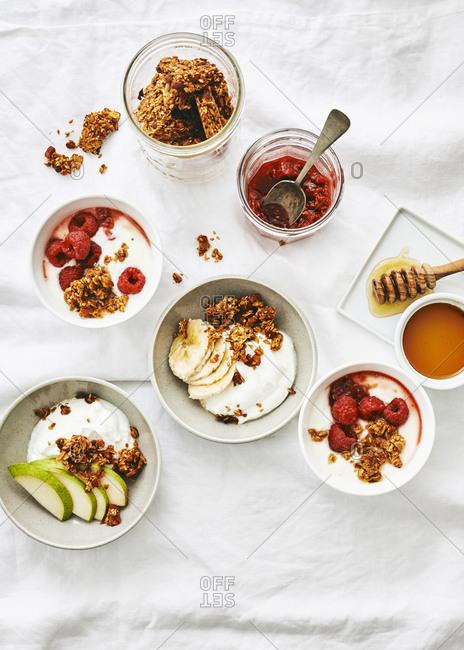Greek yogurt with fresh fruit and granola on light surface
