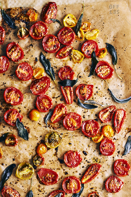 Roasted tomatoes and sage leaves on brown baking paper