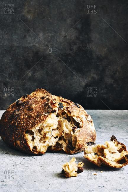 Artisanal raisin sourdough bread in front of a dark background